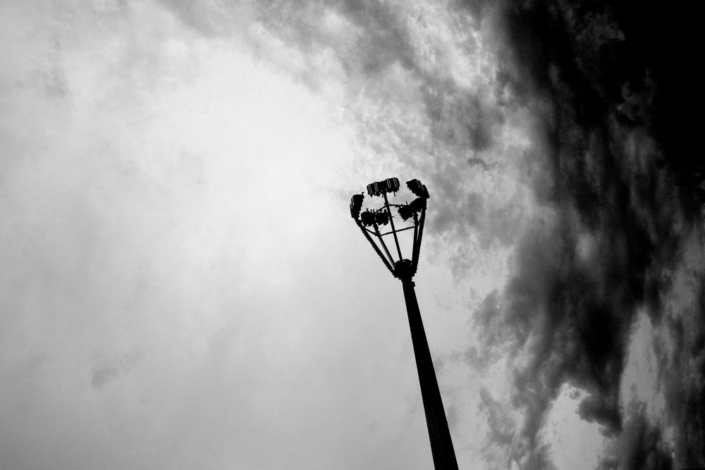 Des manèges de fête foraine sur fond de ciel d'orage