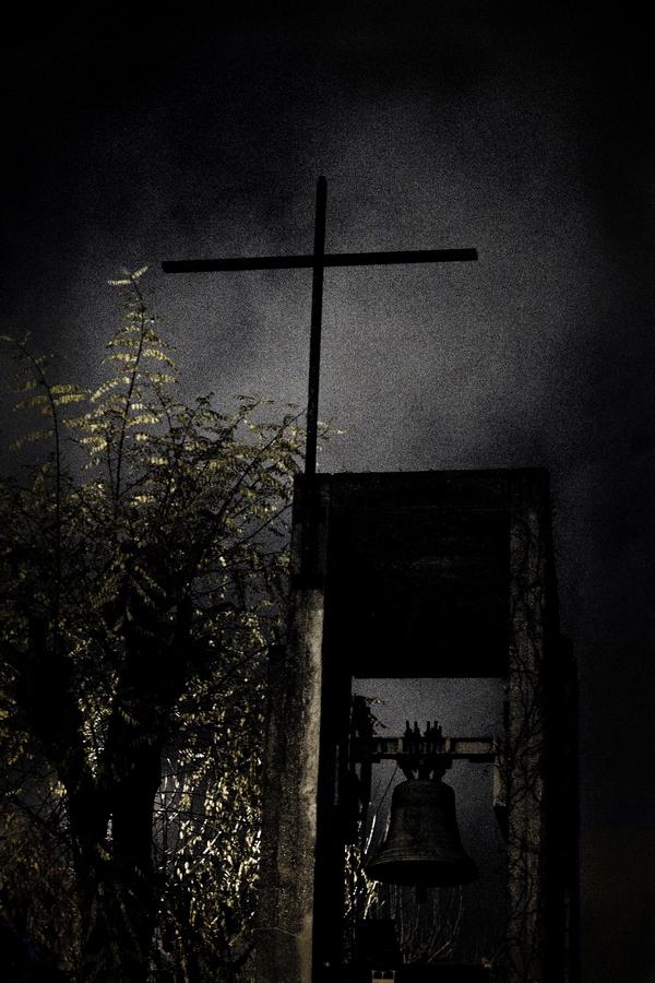 Une croix et une cloche d'église photographiees de nuit