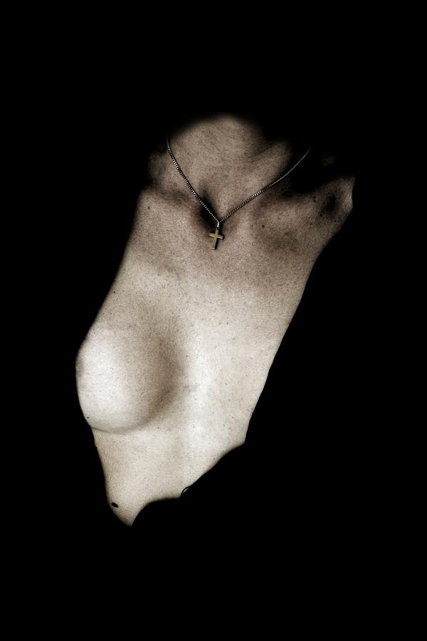 Un pendentif en forme de croix se detache sur la gorge d'une femme