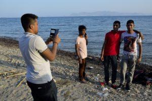 Des migrants arrivés sur une plage de Kos se prennent en photo