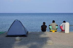 Des migrants attendent sur les quais du port de Kos Grèce