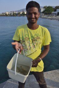 Un migrant montre sa pêche dans le port de Kos Grèce
