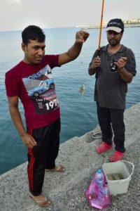 Des migrants pêchent dans le port de Kos Grèce
