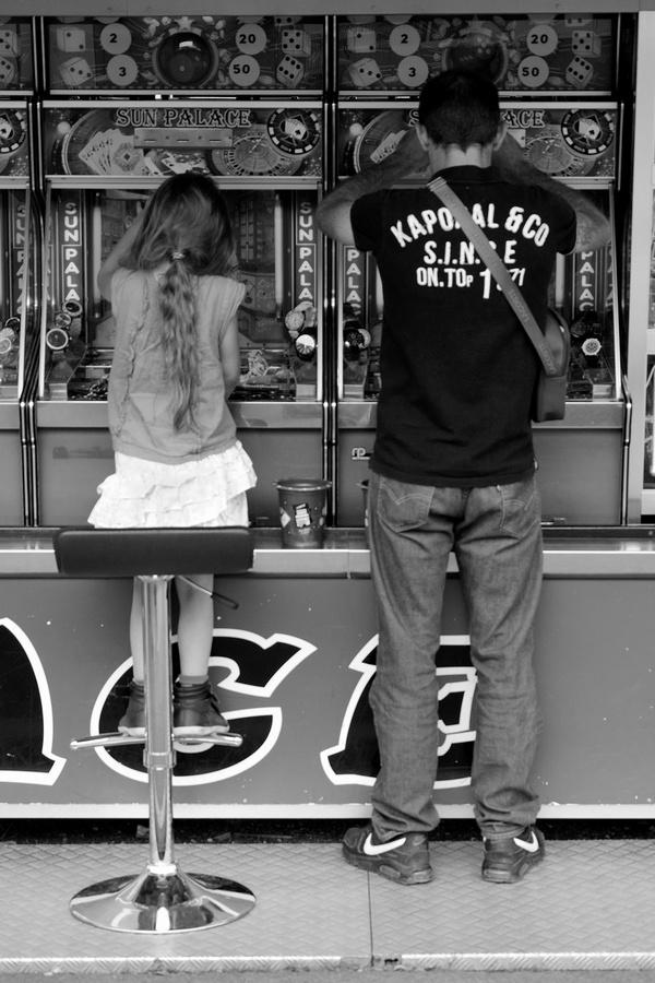 Un homme et une fillette jouant aux machines à sous