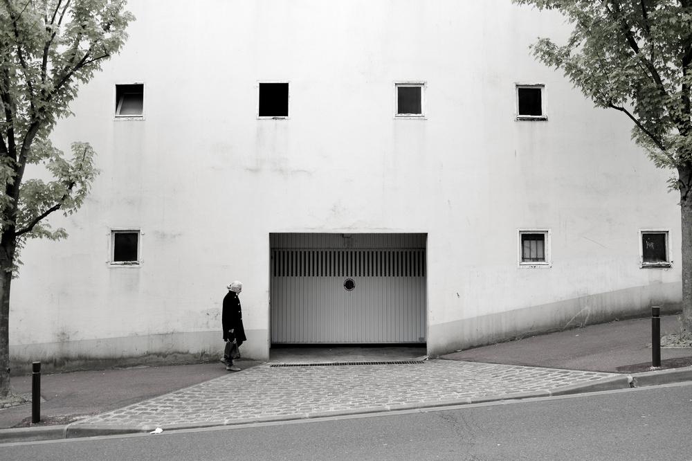 Une femme âgée monte une rue pentue