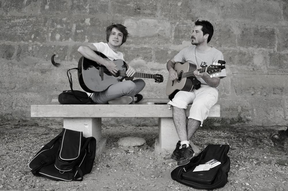 deux jeunes guitaristes assis sur un banc de pierre sur les quais de seine