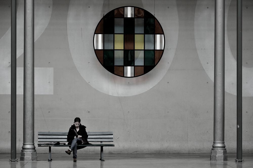 Une femme lit assise sur un banc