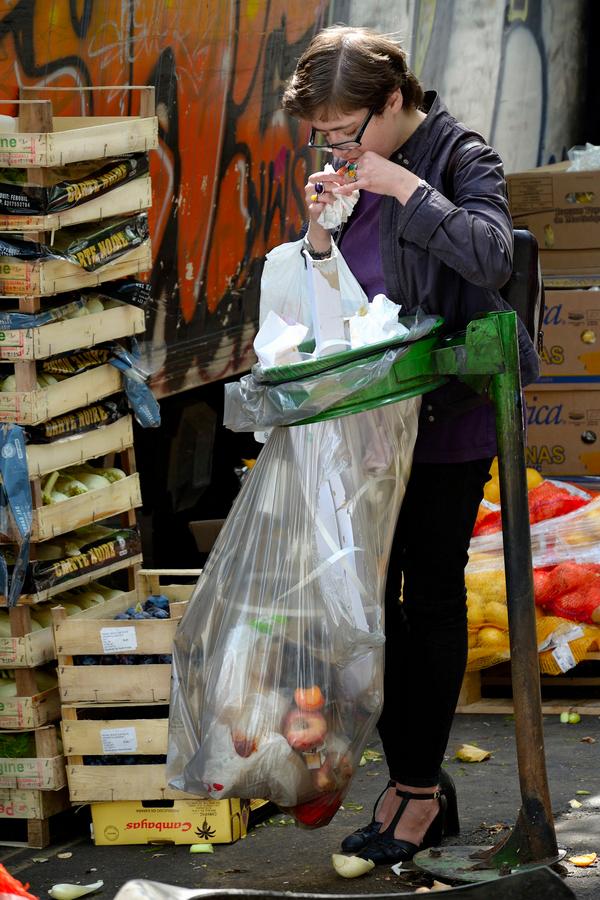 jeune femme mangeant son sandwich au-dessus d'une poubelle