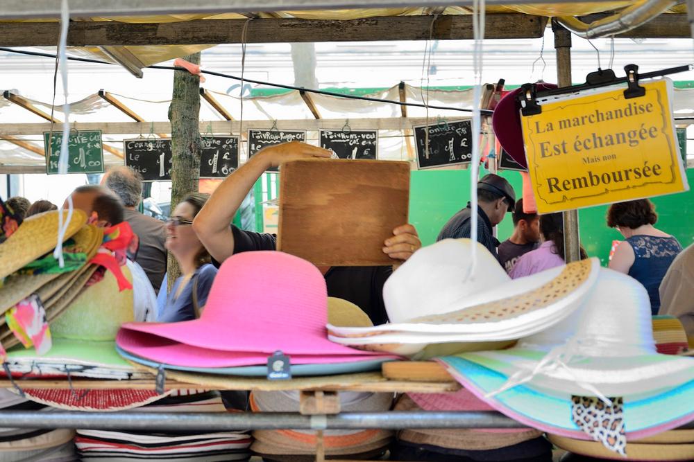 Homme essayant un chapeau dans un marché