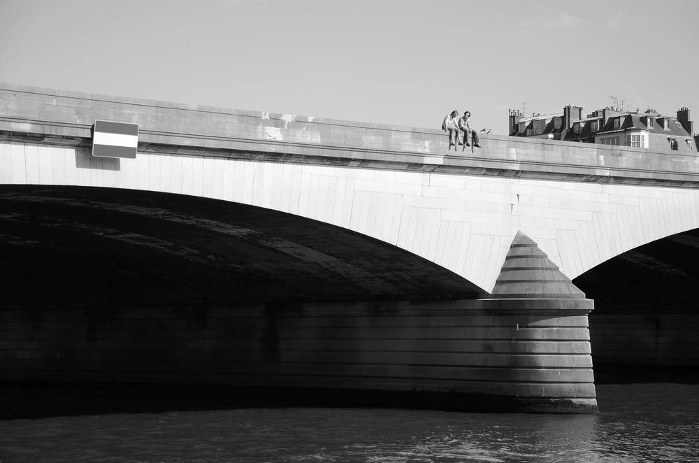 Deux personnes assises sur le parapet du pont royal a Paris