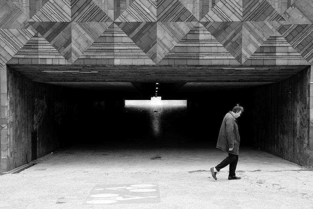 Un homme seul marche le dos voûté