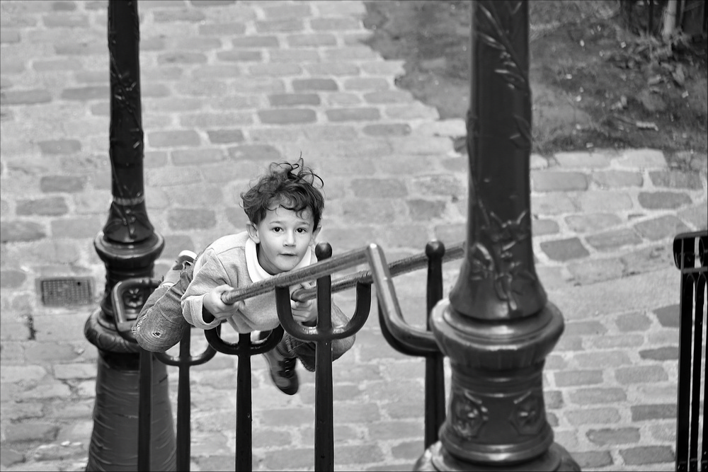 Un enfant glisse sur une rampe dans un escalier de Montmartre à Paris