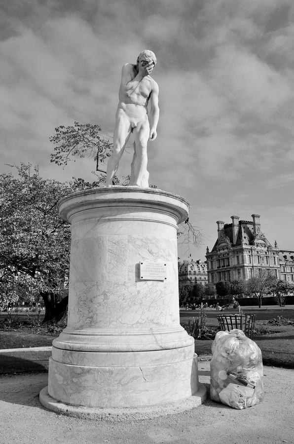 Statue de Caïn du jardin des tuileries avec une poubelle à ses pieds