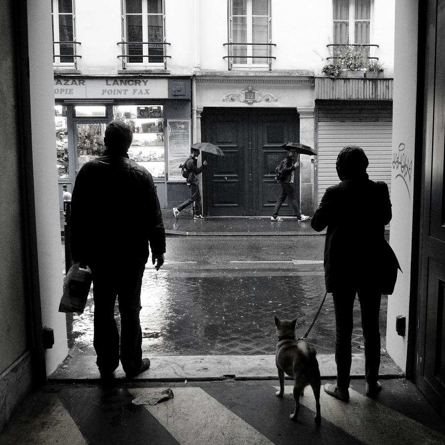 Passants dans la rue un jour de pluie