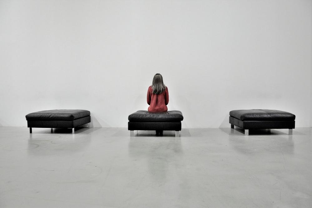 Une femme portant un pull orange assise sur un pouf noir face a un mur