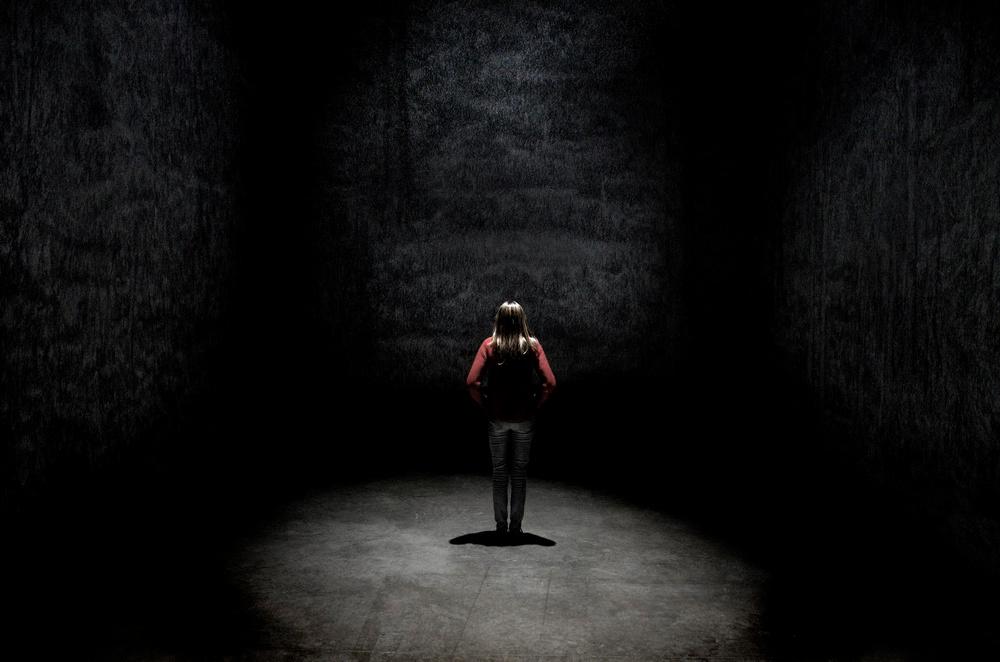Une femme portant un pull orange se tient debout dans un halo de lumière dans un espace sombre