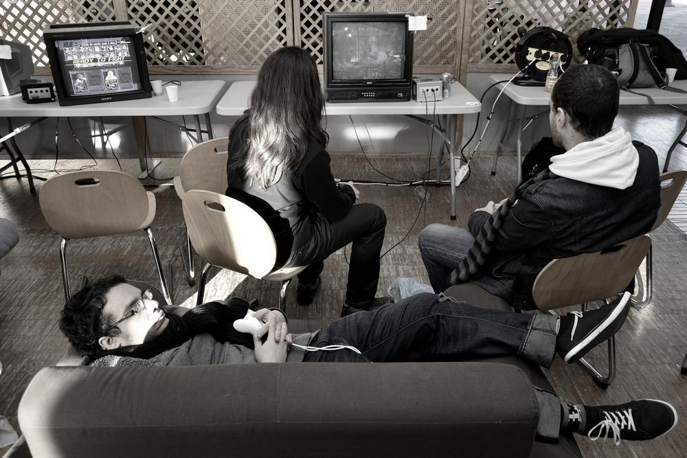 des joueurs de jeux vidéo devant une console dont un dort sur un canape