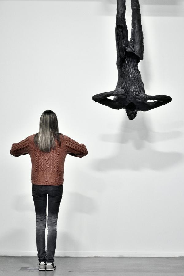 Une femme portant un pull orange imite le geste d'une statue pendant d'un plafond la tete en bas