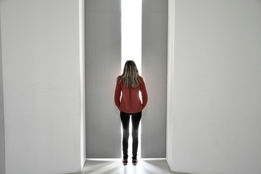 Une femme portant un pull orange debout dans la lumière