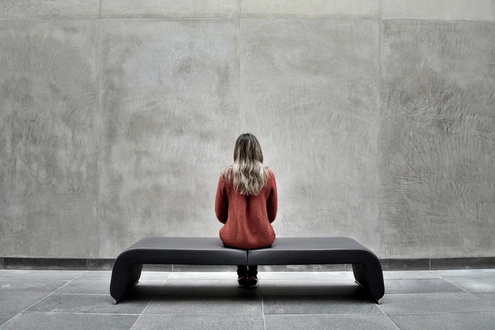 Une femme portant un pull orange assise sur un banc face à un mur