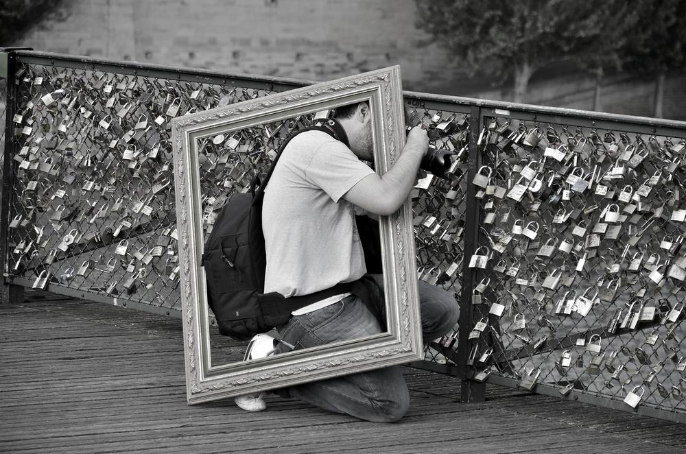 Un homme photographie les cadenas du Pont des Arts avec un cadre sur le dos
