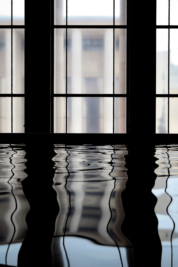Une fenêtre se reflète dans une étendue d'eau