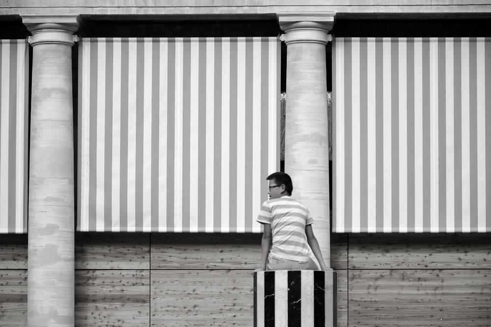 Un jeune homme avec un tshirt raye assis sur une colonne de Buren se detache sur un fond raye lui aussi