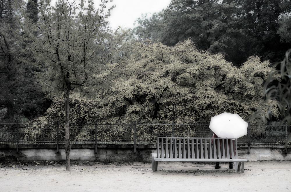 Une femme seule assise sur un banc avec un parapluie