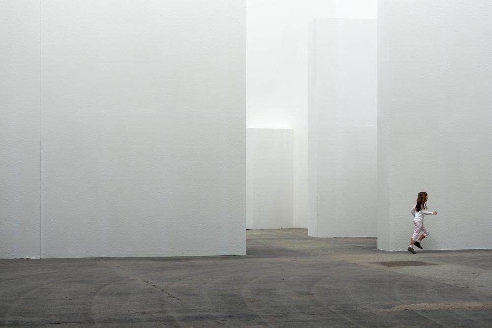 Une fillette perdue dans un grand labyrinthe blanc