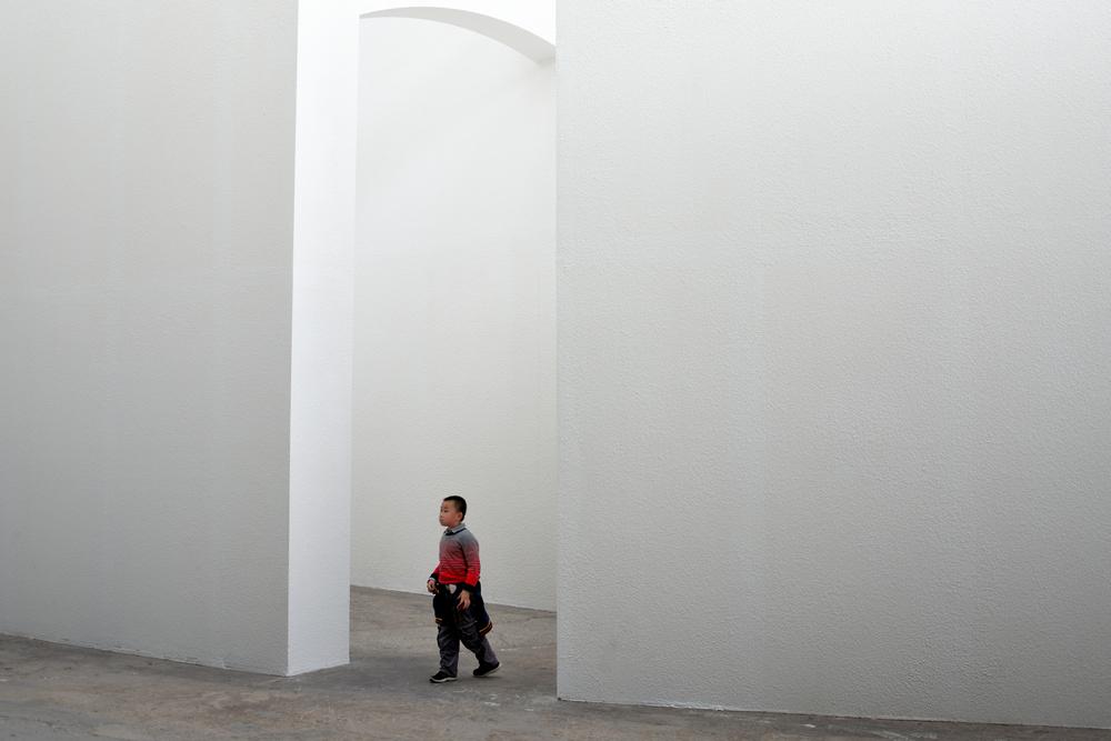 Un enfant perdu dans un grand labyrinthe blanc